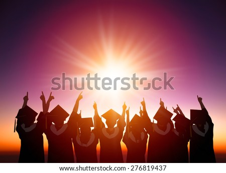 silhouette of Students Celebrating Graduation watching the sunlight - stock photo