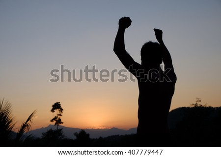 silhouette of Successful man with arm up. - stock photo