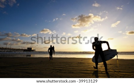 silhouette of surfers at sunset - stock photo