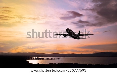Silhouette of the airplane flying in the colorful sunset sky over the mountains and water area - stock photo