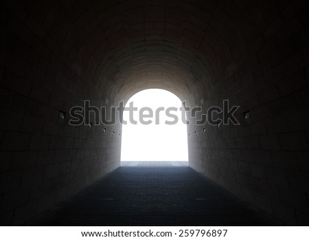 Silhouette of the archway of an underground stonemason tunnel with blank space for text, for the concept light at the end of the tunnel. - stock photo
