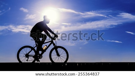 Silhouette of the cyclist riding a road bike - stock photo