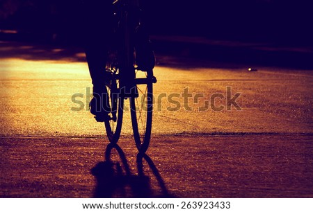 silhouette of the cyclists riding  bicycle riding on  road - stock photo
