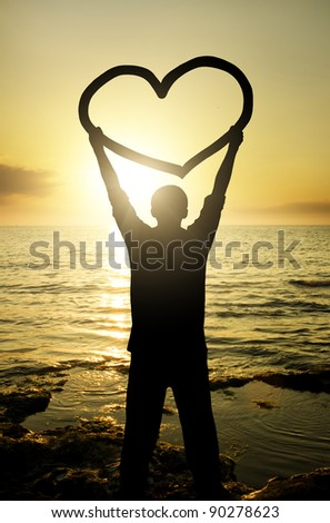 Silhouette of the enamoured young man on a decline which tries to express the feelings - stock photo