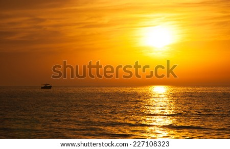 Silhouette of the fisherman or leisure boat sailing toward golden sunset with saturated sky and clouds. Beautiful seascape in the evening. Harmony with nature idea. Tranquility and freedom background. - stock photo