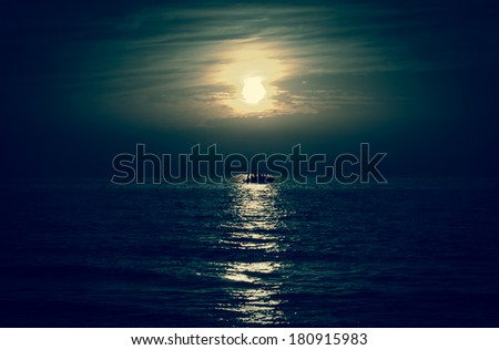 Silhouette of the fisherman or leisure boat sailing toward the moon.  - stock photo