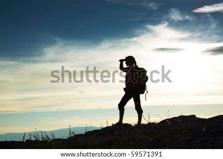 Silhouette of the girl looking in a distance against a decline - stock photo