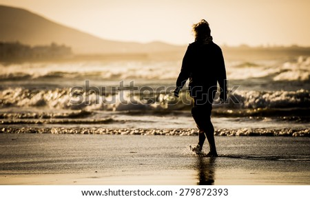 Silhouette of the man, walking on the ocean beach - stock photo