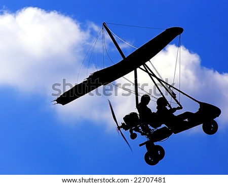 Silhouette of the Microlight Glider in the Blue Sky - stock photo