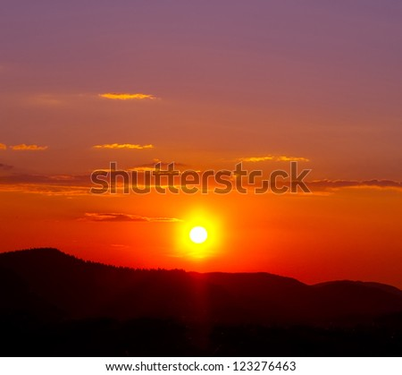 silhouette of the mountains at sunset - stock photo