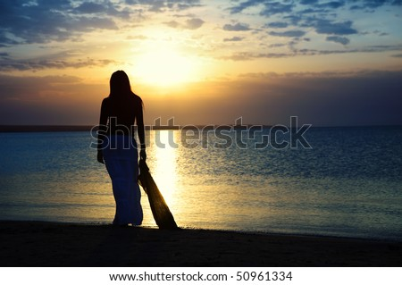 Silhouette of the single lady contemplating sunset at the beach. Vibrant color and twilight darkness - stock photo