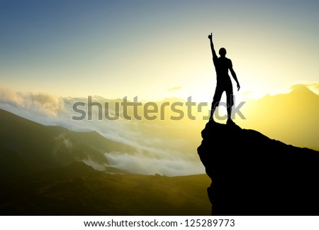 Silhouette of the winner on the high rock. Sport and active life - stock photo