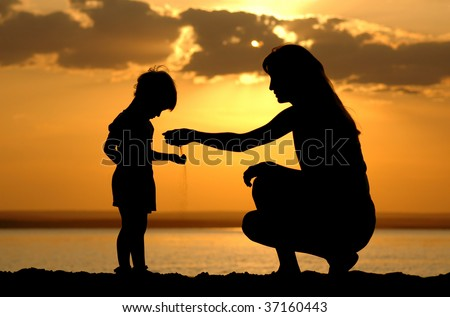Silhouette of the women to pour sand in hand child on sundown - stock photo