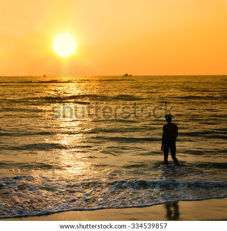 Silhouette of the young man coming into sea waves under sunset light. - stock photo