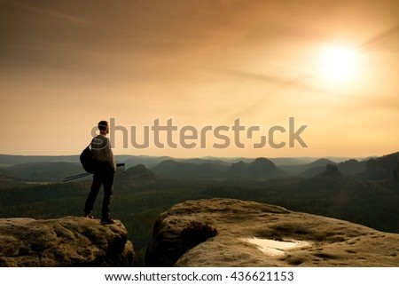 Silhouette of tourist. . Hiker with sporty backpack on rocky view point enjoying view into misty valley. Sunny spring daybreak in rocky mountains - stock photo