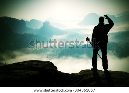 Silhouette of tourist with poles in hand. Hiker stand on rocky view point above misty valley. Sunny spring daybreak in rocky mountains - stock photo