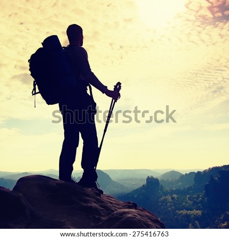 Silhouette of tourist with poles in hand. Hiker with big backpack stand on rocky view point above misty valley. Sunny spring daybreak in rocky mountains. - stock photo