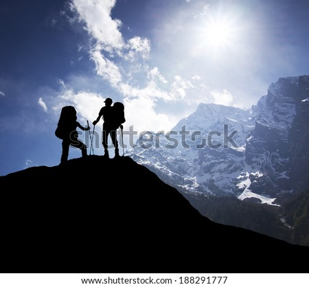 Silhouette of tourists on mountain peak. Sport and active life concept - stock photo