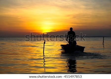 Silhouette of traditional fisherman on boat during beautiful sunrise at Labuan island,Malaysia. - stock photo