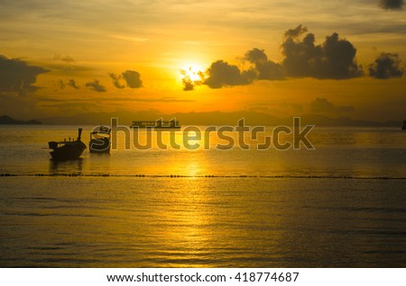 Silhouette of traditional long boat during sunset or sunrise at Andaman sea, Thailand. Concept for tropical beach, vacation, nature, relax, morning, fresh, summer, background - stock photo