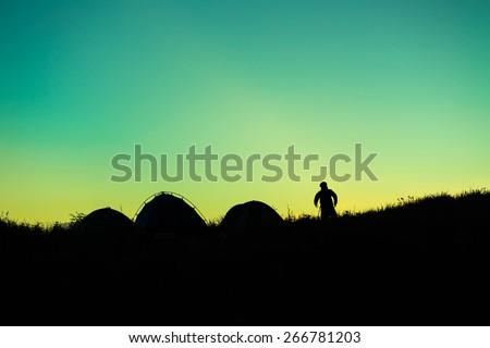 Silhouette of traveler atop a mountain.  - stock photo