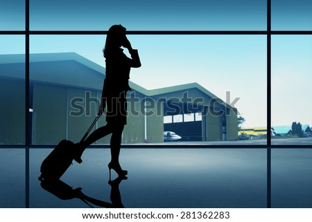 Silhouette of traveler woman walking on the airport - stock photo
