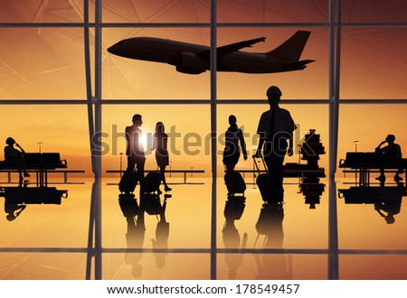 Silhouette of Travellers and Pilot at an Airport - stock photo