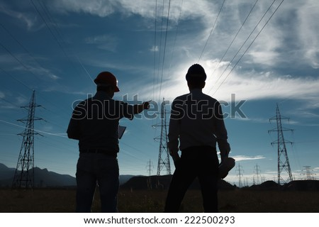 silhouette of two engineers standing at electricity station at sundown - stock photo