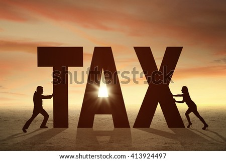 Silhouette of two entrepreneurs pushing a tax word at sunset time - stock photo