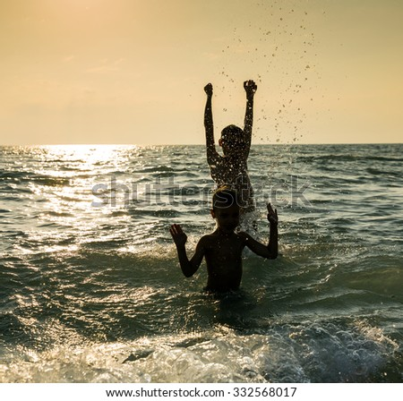 Silhouette of two happy little boy jumping in sea at sunset - stock photo