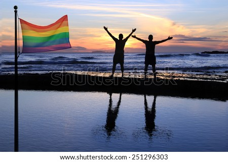 Silhouette of two men at sunset with a gay pride flag in the foreground.  - stock photo