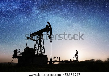 Silhouette of two oil pumps are pumping crude oil on the oil field under night sky with stars and Milky way. Oil industry equipment
