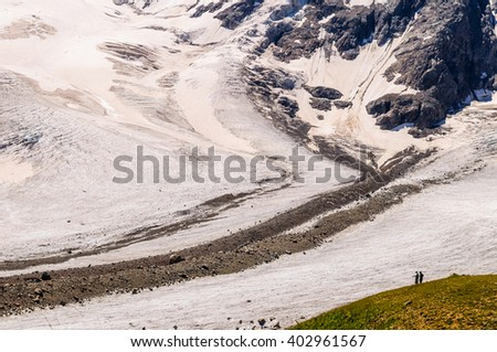Silhouette of two tourists on the background of a huge glacier in the mountains of the Caucasus, Russia - stock photo