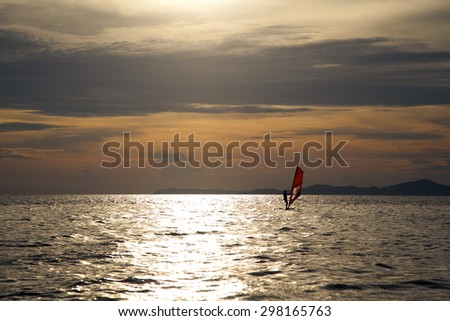 Silhouette of two windsurfers on the sea surface - stock photo