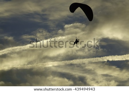 Silhouette of unidentifiable powered paraglider at sunset, with fading contrails from jet aircraft beyond, for themes of adventure, lifestyle, recreation (shallow depth of field) - stock photo