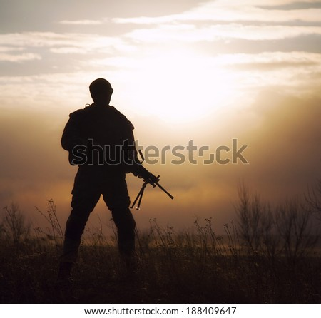 Silhouette of US marine with rifle  against the sunset - stock photo