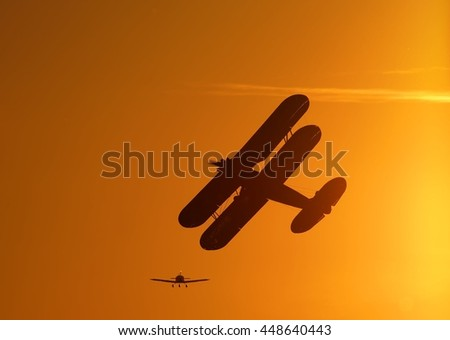 Silhouette of vintage single engine propeller biplane airplane banking left while climbing towards scenic sunset with another small aircraft flying on background detail close up view - stock photo
