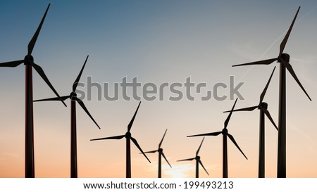 Silhouette of wind turbine in sunset sky - stock photo