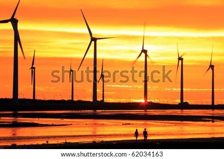 silhouette of wind turbines at sea shore - stock photo