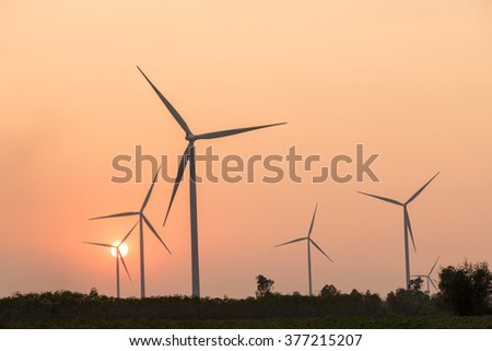 silhouette of wind turbines power generator at sunset - stock photo