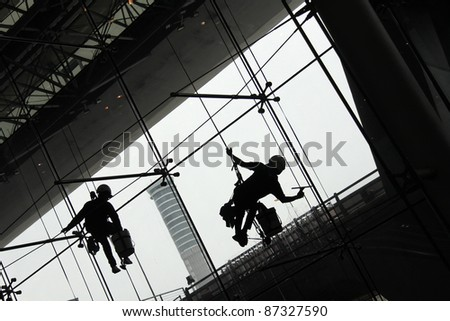 silhouette  of Window Cleaners (Window washers) working - stock photo