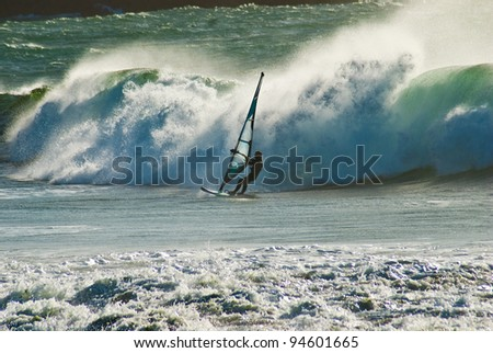 Silhouette of windsurfer racing a breaking wave in the early evening on the Coast of Death in Galicia, Spain - stock photo