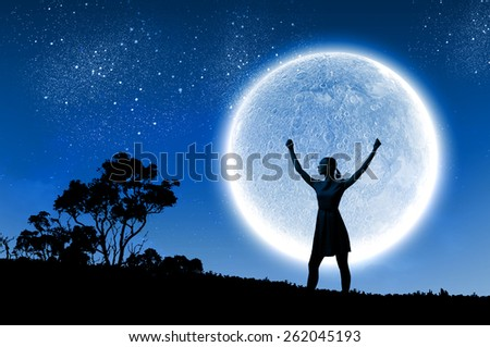 Silhouette of woman against full moon with hands up - stock photo