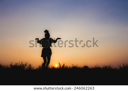silhouette of woman at sunset , jump posture , near Dim atmosphere - stock photo