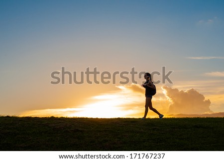 Silhouette of woman backpacking through the countryside. - stock photo