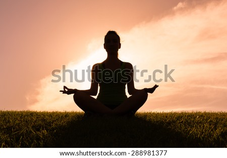 Silhouette of woman doing yoga. - stock photo
