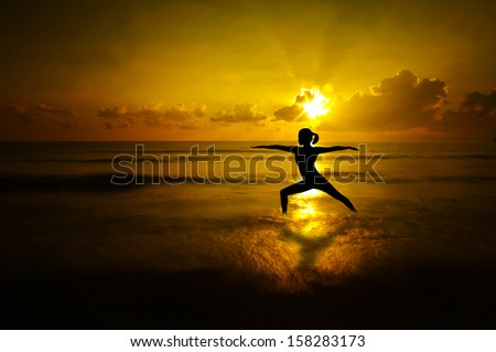 Silhouette of woman doing yoga meditation during sunrise with natural golden sunlight at beach. - stock photo
