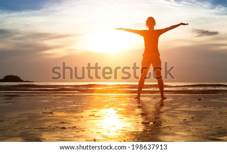 Silhouette of woman exercise on the beach at sunset. - stock photo