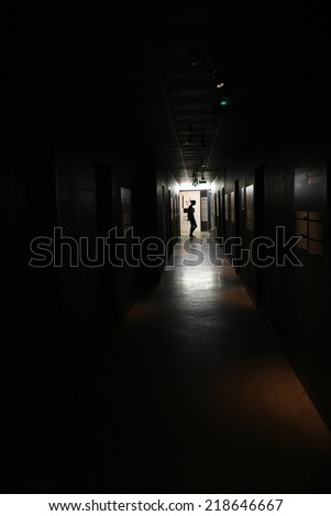 Silhouette of woman in the end of long corridor - stock photo