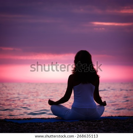 Silhouette of Woman Meditating in Lotus Position by the Sea at Sunset. Rear View. Nature Meditaion Concept. Toned Instagram Styled Photo. - stock photo